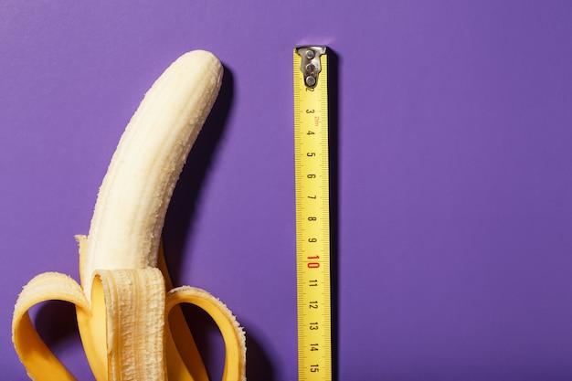 Измерение размера банана с помощью линейки от колеса рулетки на фиолетовом фоне, как символа мужского полового члена.