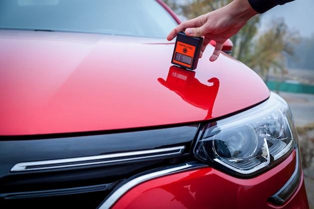 塗装厚さ計を使用して、自動車の塗装コーティングの赤色の厚さを測定します。