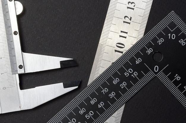 측정 도구, 눈금자 사각형 및 캘리퍼스. 어두운 배경에 누워. 확대.