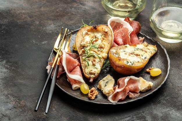 Мясно-сырная тарелка закуска закуска к вину с грушей, запеченная с дорблю, горгонзолой, рокфором, ветчиной прошутто. баннер, меню, место рецепта для текста, вид сверху.