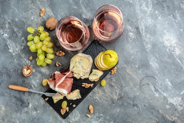 Мясно-сырная тарелка закуска закуска к вину с ветчиной прошутто, голубым сыром, виноградом, грецкими орехами и грушей. баннер, меню, место рецепта для текста, вид сверху