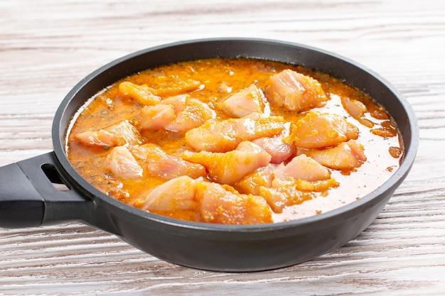 鍋に肉とカレーソース。チキンカラヒ。インドのスパイシーチキンカレー。ステップバイステップで調理