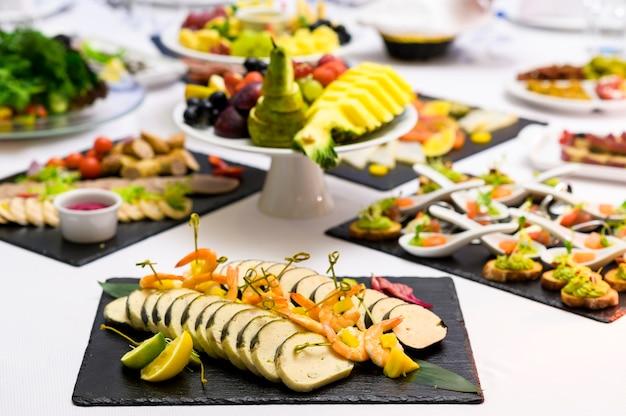 宴会テーブルとプレート上のレストランでの肉と魚のスライス