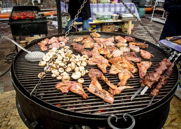 야외 주방에서 큰 바베큐에 요리하는 고기와 버섯