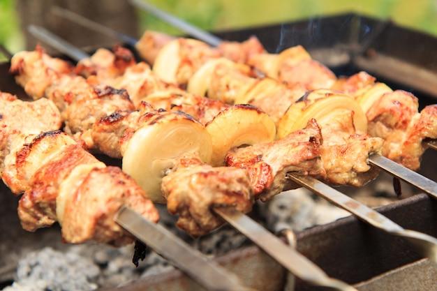 꼬치에 꽂힌 고기와 양파를 숯불에 굽고 있습니다. 바베큐에서 시시 케밥 요리. 피크닉, 길거리 음식. 선택적 초점