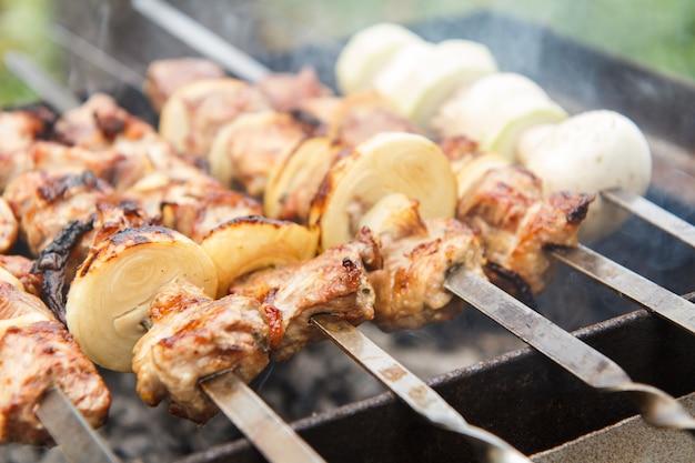 꼬치에 고기와 양파, 꼬치에 호박과 버섯이 숯불에 구워지고 있습니다. 바베큐에서 시시 케밥 요리. 피크닉, 길거리 음식. 선택적 초점