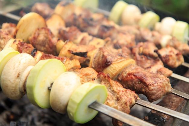 꼬치에 고기와 양파, 꼬치에 호박과 버섯을 숯불에 굽고 있습니다. 바베큐에서 시시 케밥 요리. 피크닉, 길거리 음식. 선택적 초점