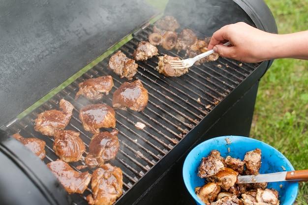 Мясо и сосиски на гриле на открытом воздухе на лужайке зеленой травы. человек готовит