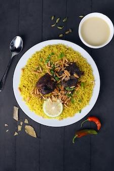 黒の背景に肉と黄色の米アラビア米