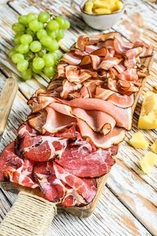 Meat antipasto board, pancetta, salami, sliced ham, sausage, prosciutto, bacon