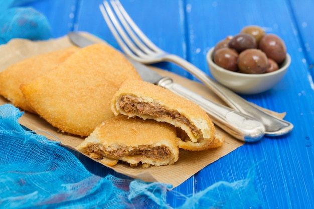 Мясная закуска на бумаге на синей деревянной поверхности