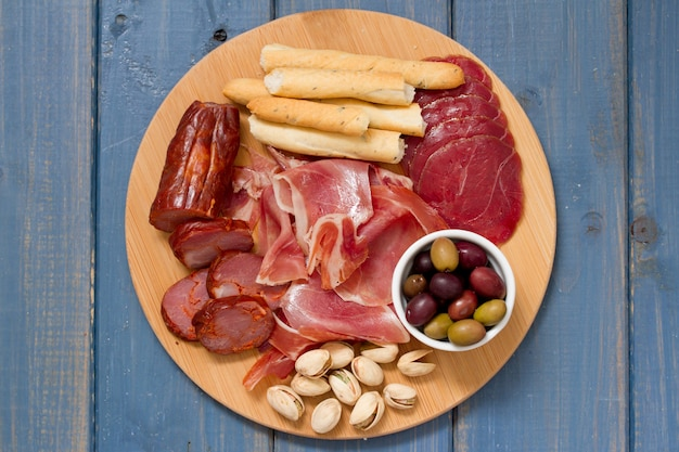 Meat appetizer with olives and nuts on tray on blue wooden surface