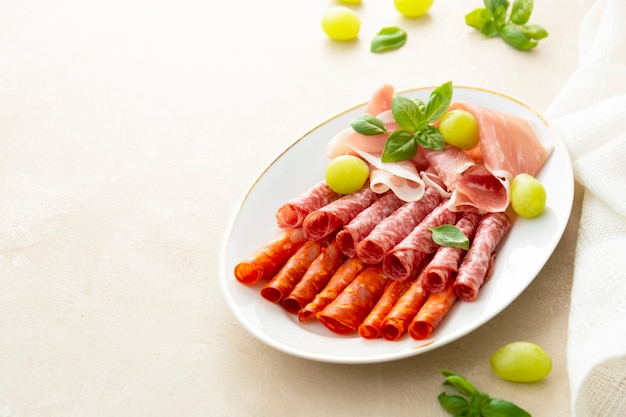 Meat assortment, salami slices in plate, with basil and grapes, copy space. delicious snack for wine.