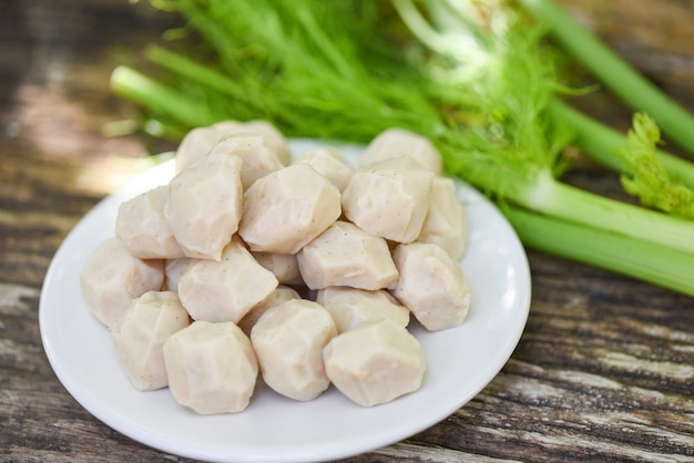 Мясной шарик на белой тарелке и овощах на деревянном фоне, мясной шарик со свининой и ингредиентом