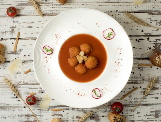 Meat ball soup in tomato sauce inside a white bowl plate.