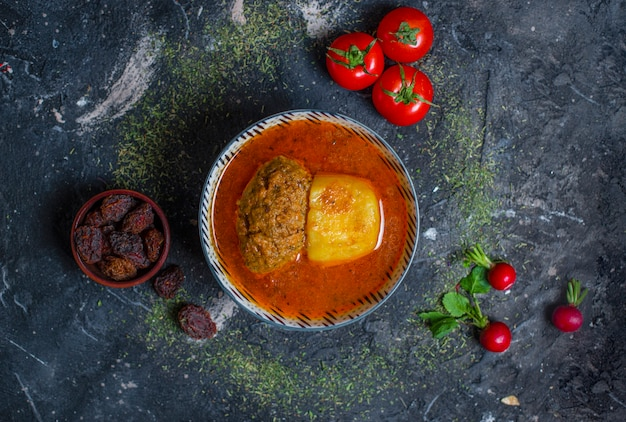 Meat ball soup with potatoes with tomato sauce, dry fruits, tomatoes on stone background