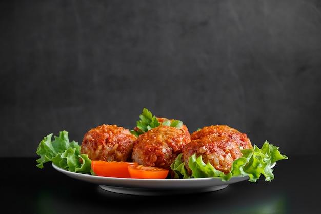 검은 공간에 토마토 소스에 고기 공. 건강한 다이어트를위한 수제 단백질 식사.