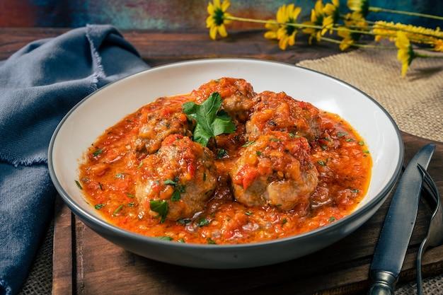 둥근 접시에 토마토 소스를 곁들인 미트볼이나 미트 로프. 높은 전망