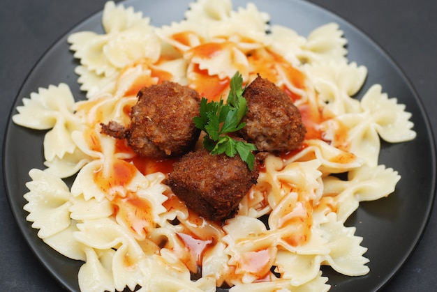 Meat balls with farfalle pasta, dark.