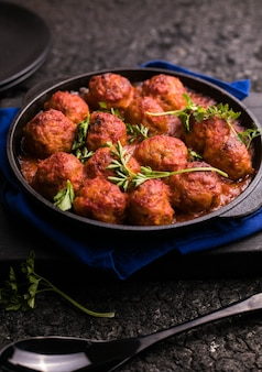 Meat balls with tomato sauce  in a frying pan on a black surface.