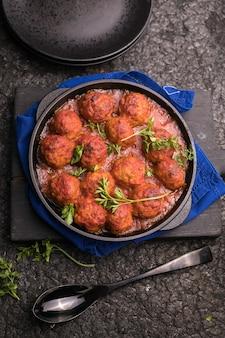 黒い表面のフライパンにトマトソースをかけたミートボール。