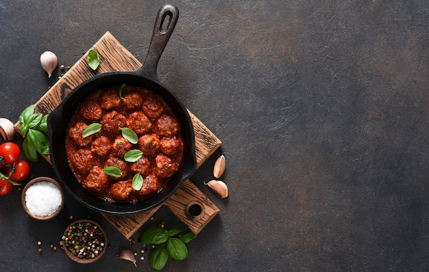 Meat balls with tomato sauce with garlic and basil in a frying pan on a brown surface.