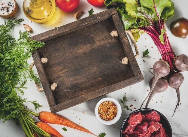Мясо, говядина. свежий сырой нарезанный гуляш, кубики говядины в миску. специи (соль, перец), помидоры, чеснок, лук. на белом мраморном столе, с вилкой для мяса и ножом. вид сверху