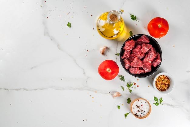 Мясо говядины свежие сырые рубленые кусочки говядины гуляш в миске специи (перец соленый) помидоры лук чеснок на белом мраморном столе с вилкой для мяса и ножом
