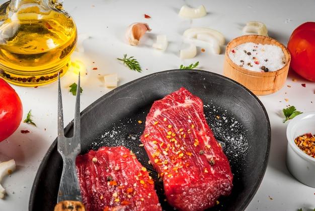 Мясо, говядина. свежие сырые стейки в сковороде. специи (соль, перец), свежие овощи, помидоры, морковь, чеснок, лук. на белом мраморном столе, с вилкой для мяса и ножом.