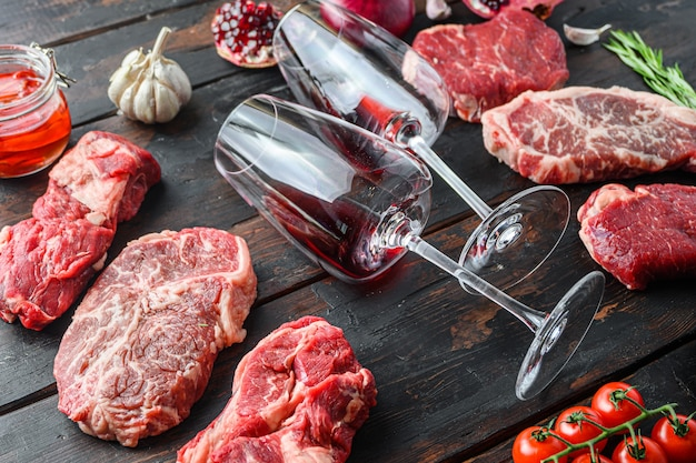 고기 쇠고기 스테이크 프레임 개념, 다른 스테이크 컷과 짙은 오래된 나무 테이블 측면 전망에 프레임에 두 개의 와인 잔이 있습니다.