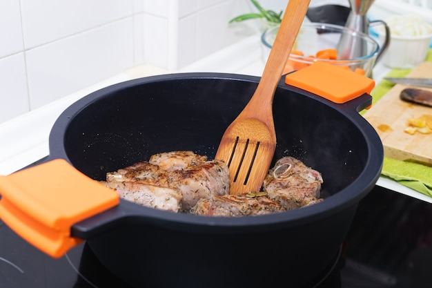 Meat being cooked in a black pot with wooden utensil. cooking concept.