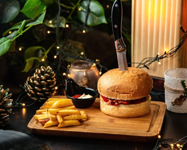 Meat burger served with french fries and mayonnaise