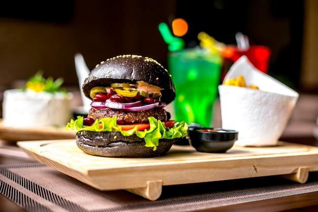 Vista laterale dei jalapenos della lattuga della cipolla del pomodoro dell'hamburger della carne