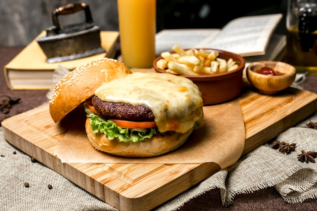 Meat burger on wooden board lettuce tomato cheese french fries ketchup side view