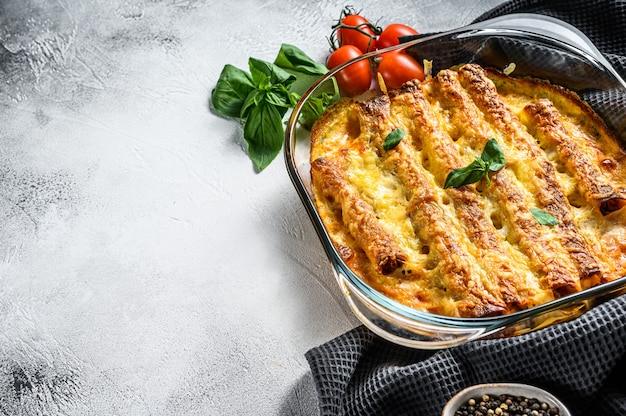 Мясные каннеллони с томатным соусом и сыром. итальянская кухня. серый фон вид сверху. копировать пространство