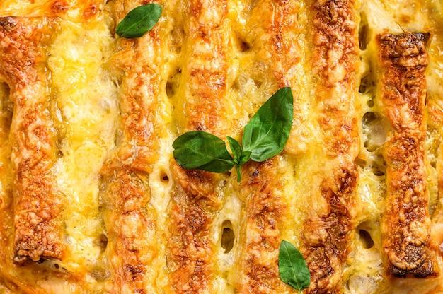 Мясные каннеллони с томатным соусом и сыром. итальянская кухня. серый фон вид сверху
