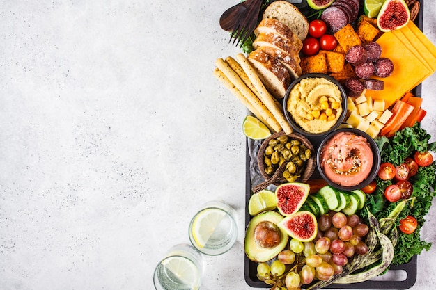 Meat and cheese appetizer platter. sausage, cheese, hummus, vegetables, fruits and bread on black tray.