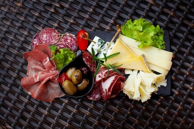 Meat and cheese appetizer with pickled olives and lettuce leaves.