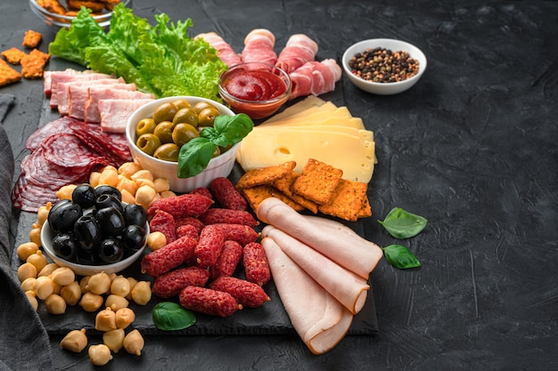 Meat and cheese appetizers with olives and salad on a flat slate board. side view with copy space.