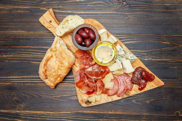 Meat and cheese plate with salami sausage, chorizo, parma and brie cheese