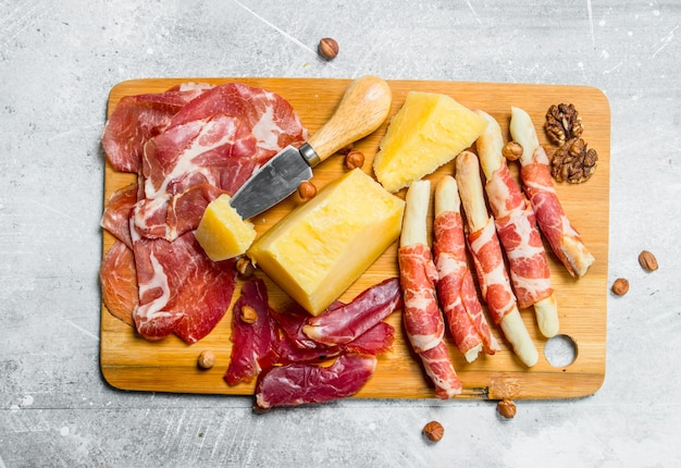 Meat and cheese snacks on board on rustic table.