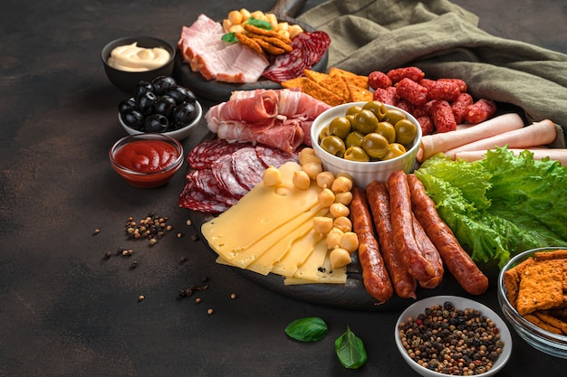 Meat and cheese snacks with salad and olives on a brown background