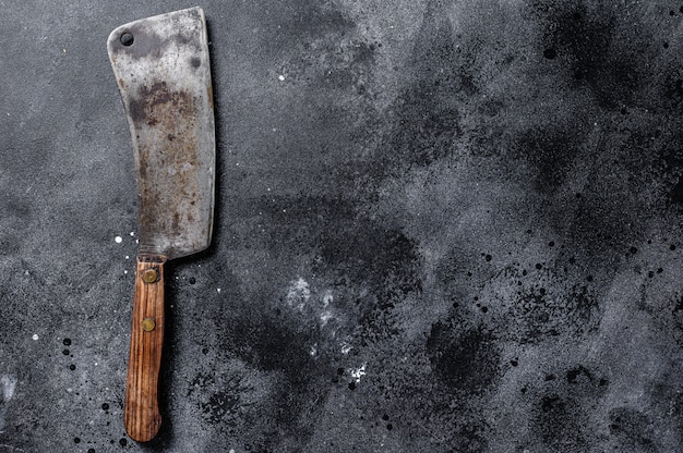 Meat cleaver on old scratched black  texture.  dark background. top view. copy space