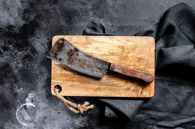 Meat cleaver on old scratched wooden cutting board. dark background. top view.