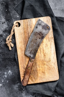 Meat cleaver on old scratched wooden cutting board. dark background.
