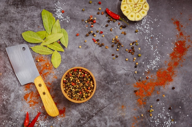 Meat cleaver and spices on dark background. top view.