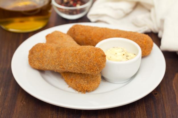 Мясные крокеты с соусом на белой тарелке