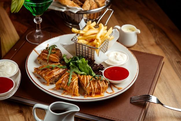 フライドポテトケチャップマヨタルフンレモネードとテーブルの上のパンと肉のカツレツ