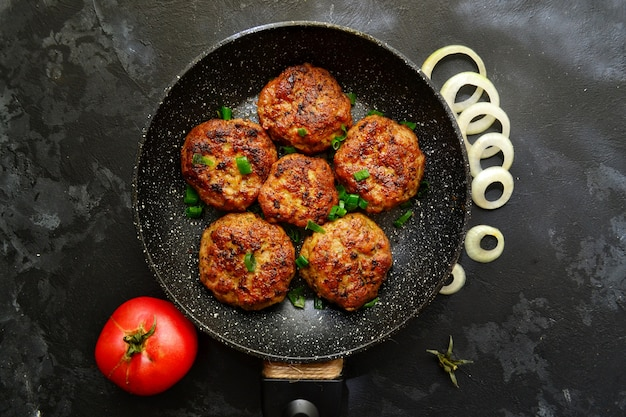 Meat cutlets. cutlets in a pan on a black concrete table.. delicious tasty food. top view