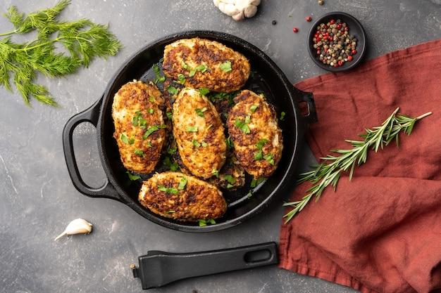 Мясные котлеты на сковороде на фоне зелени и специй, вид сверху, плоская кладка, фото высокого качества